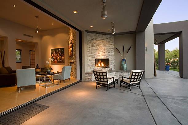 stühle am offenen kamin auf der terrasse - luxuriöse inneneinrichtung stock-fotos und bilder