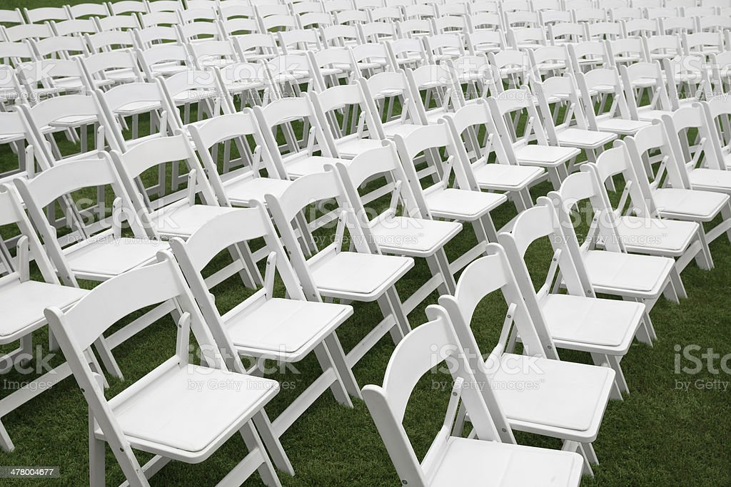Lots of white chairs in rows on a lawn.