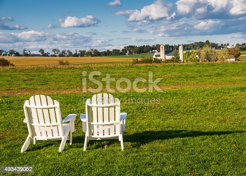 Two white Adirondack  chairs are set out on a pasture in Intercourse Pennsylvania inviting passer bys to stop for a moment and enjoy the view.