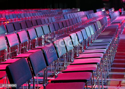Series of empty chairs lined up in conference venue