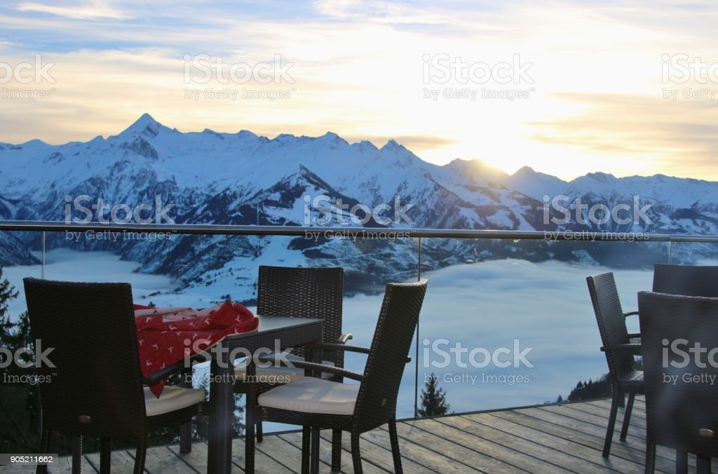 Chairs on a terrace of a cafe in the mountains and view of the Hohe Tauern mountain range. Zell am See, Austria. stock photo
