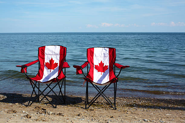 chairs with canadian flag by the lake - canada day stock pictures, royalty-free photos & images
