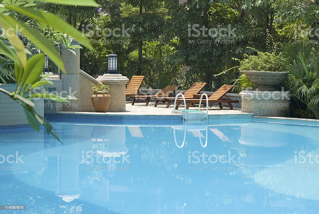 Chaise longue and swimming-pool stock photo