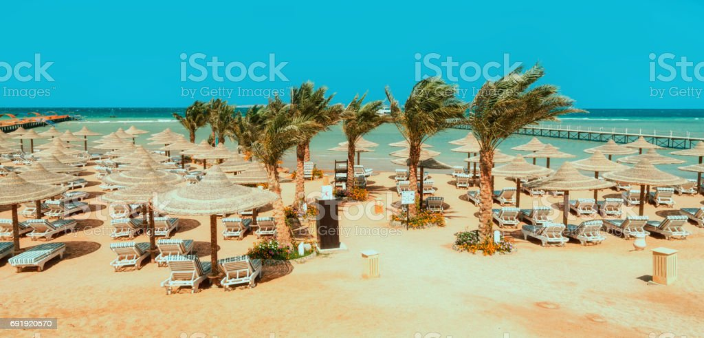 Chaise lounge and parasols on the beach against the blue sky and sea. Egypt, Hurghada stock photo