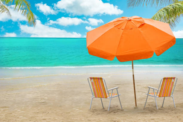Chaise lounge and umbrella on beach stock photo