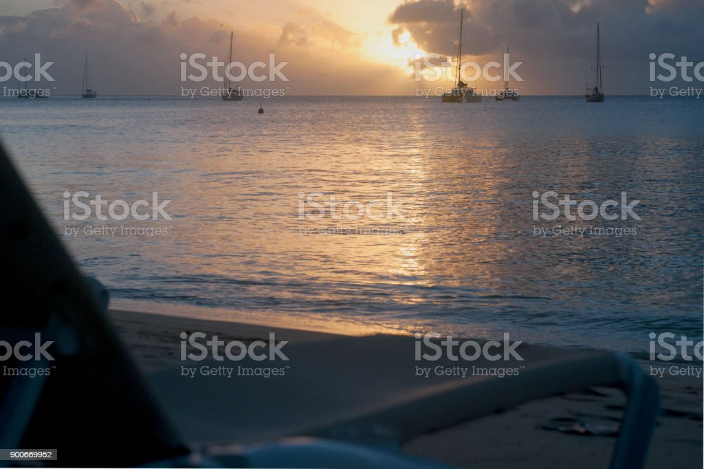 chaise-longue on the sand beach and yachts stock photo