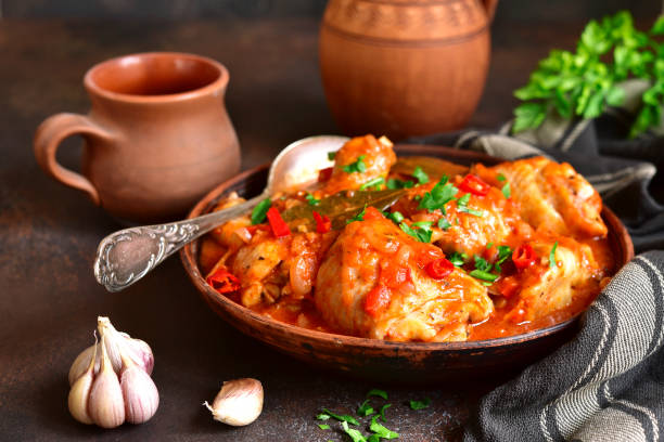 Chakhokhbili - chiken stew with cilantro (parsley) in tomato sauce Chakhokhbili - chiken stew with cilantro (parsley) in tomato sauce in a clay bowl,traditional dish of georgian cuisine stew stock pictures, royalty-free photos & images