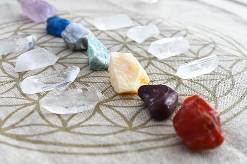 A close up image of chakra balancing crystals on a sacred geometry grid cloth.