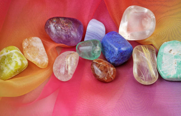 Chakra healing gemstones on Rainbow Chiffon Material Background A selection of tumbled chakra gemstones laying on rainbow chiffon material crystal healing stock pictures, royalty-free photos & images