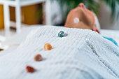 Healing and Balancing Chakras Therapy. Beautiful elderly woman lying on massage table and enjoying heart chakra healing treatment