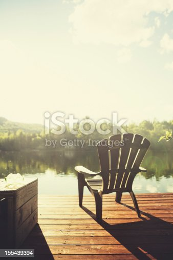 Adirondack chair on a jetty in front of a quiet lake at sunset. Visible lens flares.