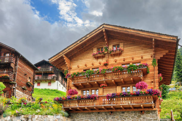 Chalet with geraniums in Grimentz Beautiful traditional wooden houses in the alpine village Grimentz, Switzerland, in the canton Valais, municipality Anniviers, with geranium flowers on the balconies swiss culture stock pictures, royalty-free photos & images