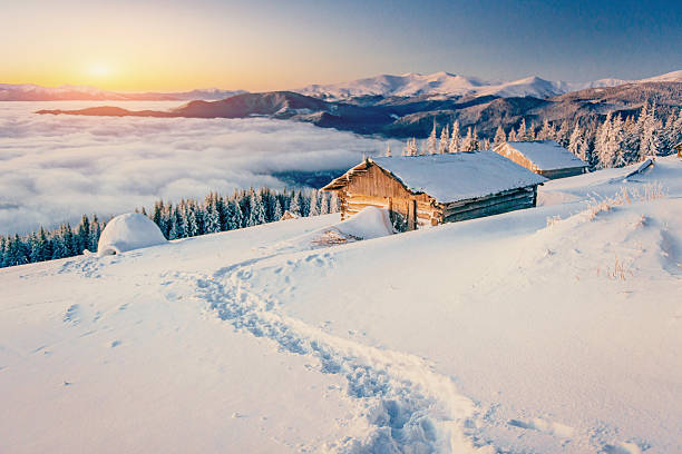 chalets in the mountains at sunset stock photo
