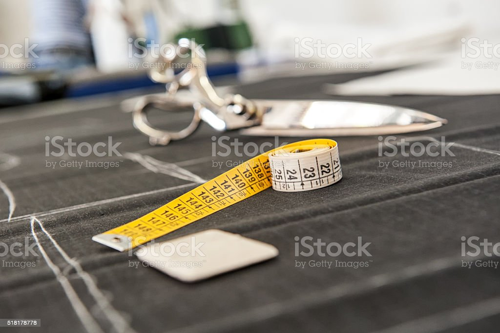 Chalk and a tape measure on uncut fabric stock photo