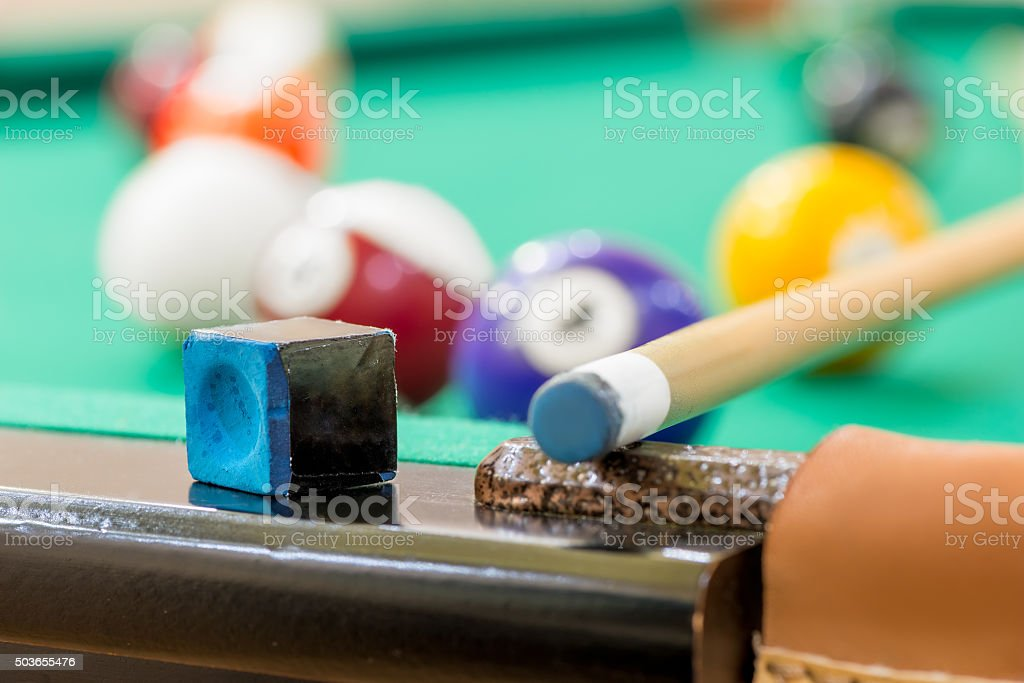 chalk and cue on edge of the table of billiard stock photo