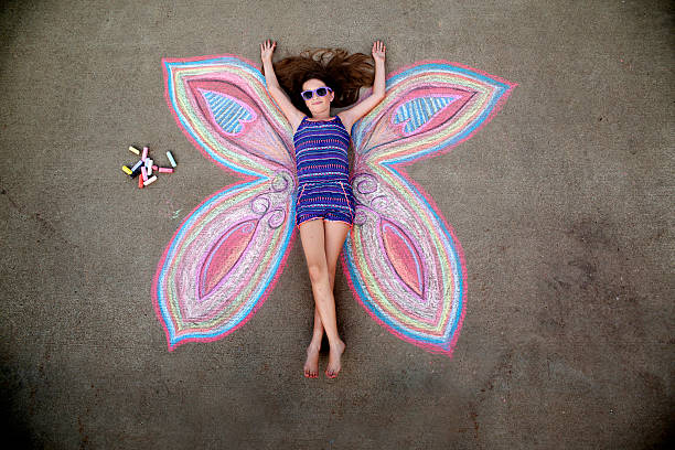 Chalk Art Portrait A 10 year old girl poses as the center of a butterfly drawn on the sidewalk with chalk. chalk drawing stock pictures, royalty-free photos & images