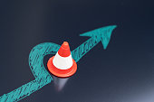 istock Chalk drawing arrow turn or break through road block traffic pylon on dark blackboard using as obstacle, solution for business problem or break through to success concept 1205888411