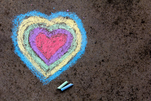 chalk drawing: colorful hearts on asphalt - chalk drawing stock photos and pictures