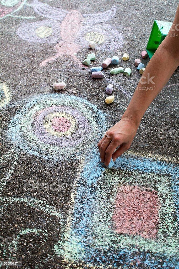 Chalk drawing hand outside on asphalt, woman hand..