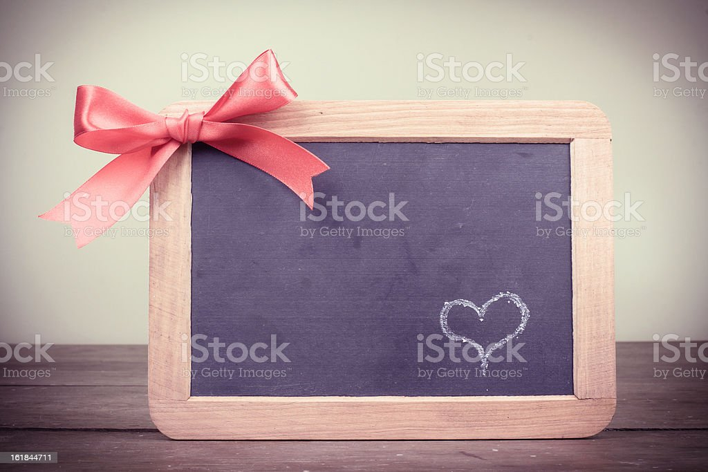 Chalk heart on board with bow in vintage style royalty-free stock photo