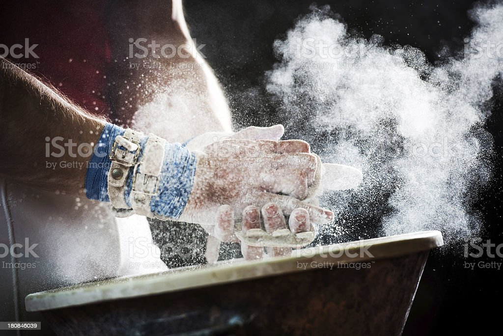 Chalk powder flies as gymnast prepares for bars. royalty-free stock photo