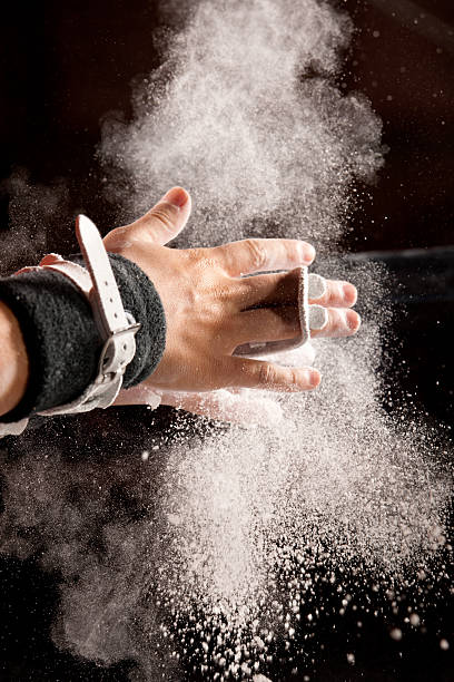 chalk powder flies as gymnast preps for bars - uneven parallel bars stock photos and pictures