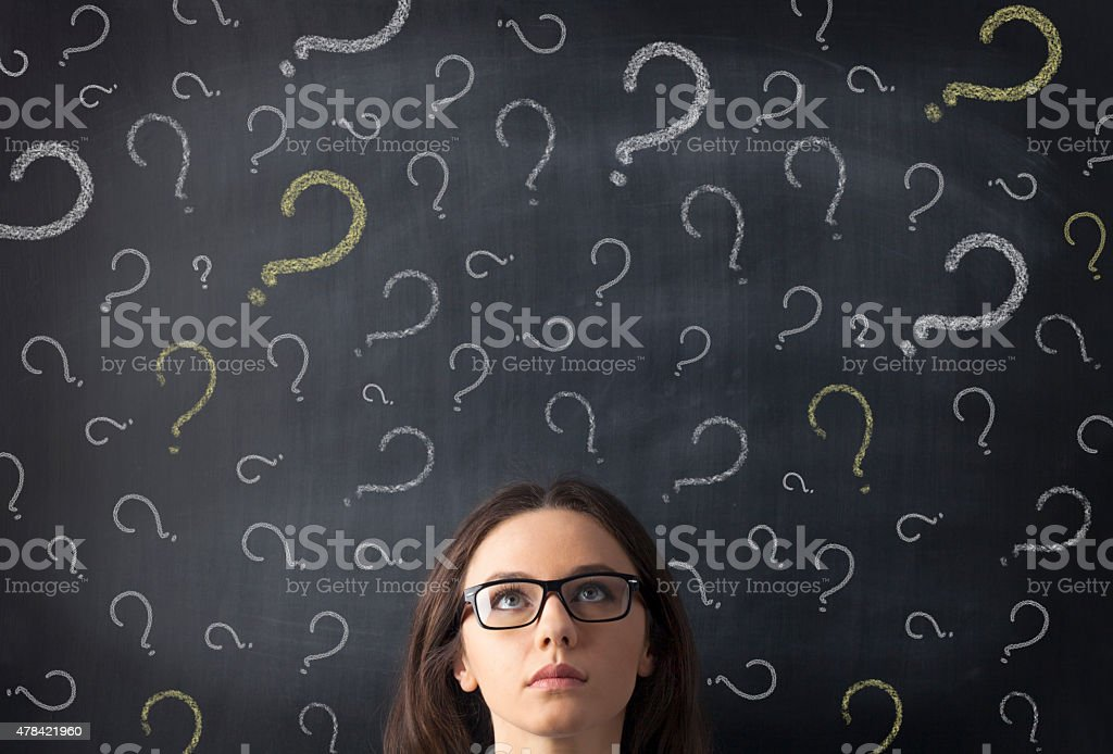 Chalk question marks above businesswoman at blackboard stock photo