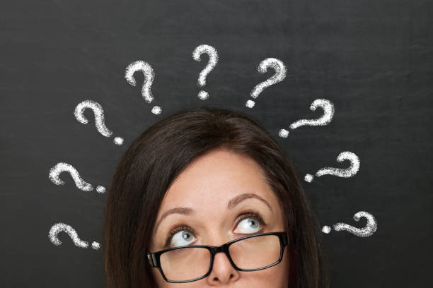 Chalk question marks above woman at blackboard Chalk question marks above woman at blackboard raised eyebrows stock pictures, royalty-free photos & images
