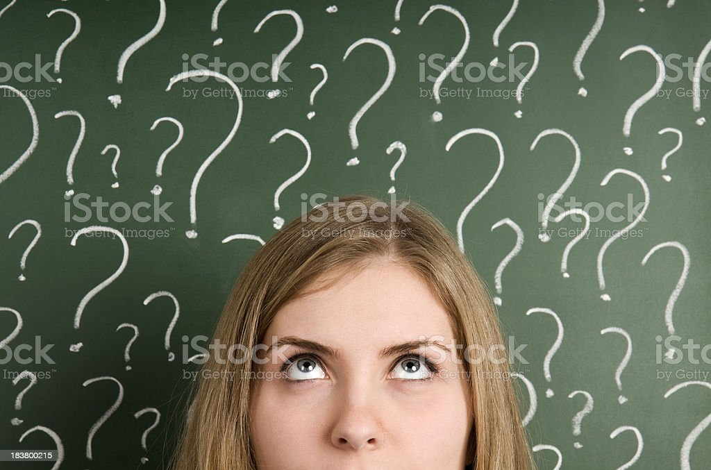 Chalk question marks above woman at blackboard royalty-free stock photo