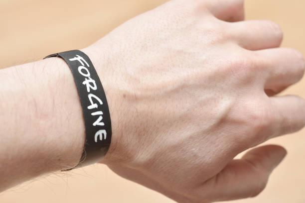 kreide-armband mit verzeihen nachricht - canda armband stock-fotos und bilder