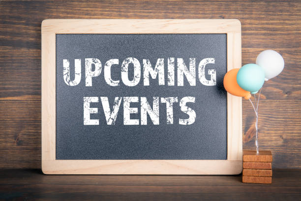 UPCOMING EVENTS. Chalkboard and colored balloons on a wooden background stock photo