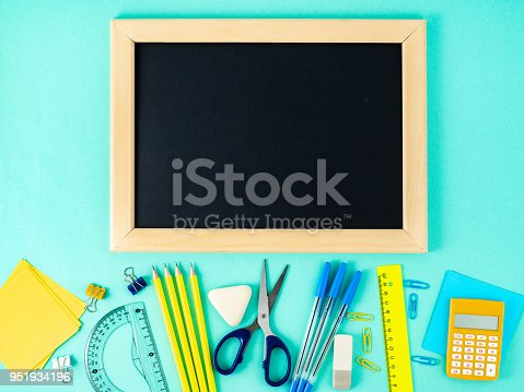 istock Chalkboard and school supplies on white table by the blue wall. Top view, flat lay, empty space for text. Back to school concept. 951934196