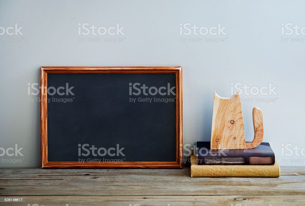 chalkboard frame on the grey wall with books and cat