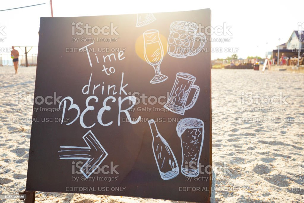 chalkboard in the sun rays on the beach with text: Time to drink beer Marbella, Spain 2018-07-29 – zdjęcie