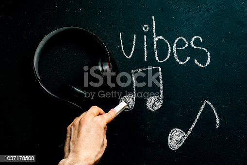 chalkboard music concept with headphones and vibes word with music notes