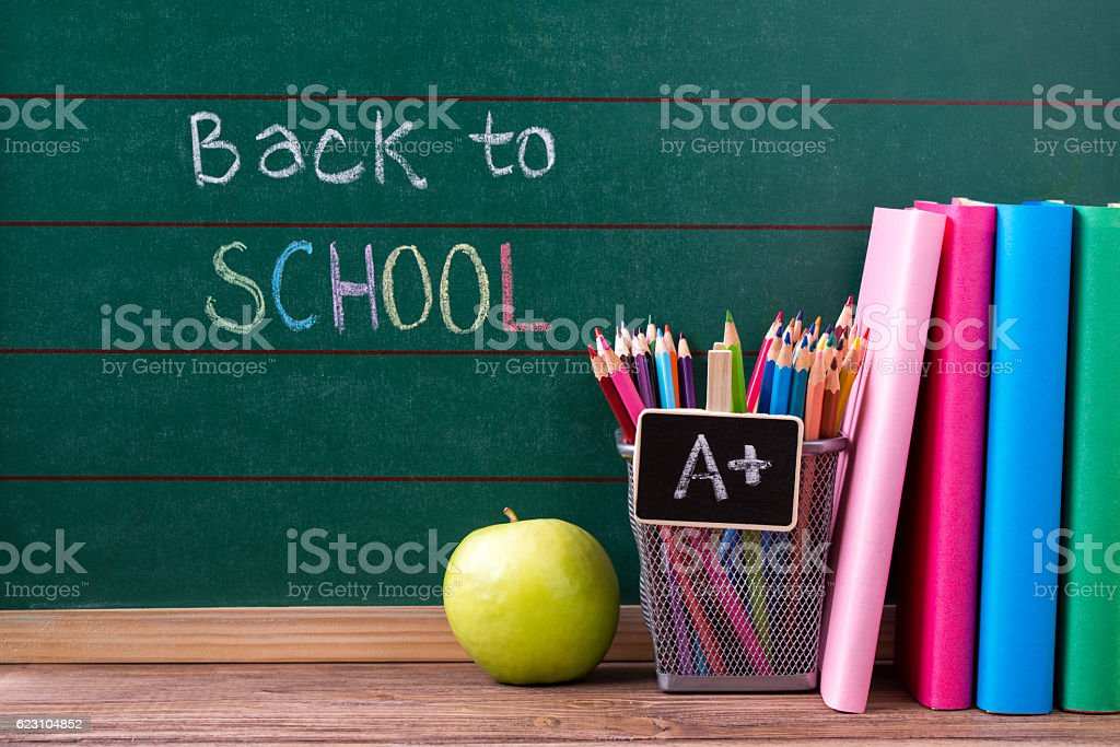 Chalkboard with back to school written, books, apple and pencils stock photo