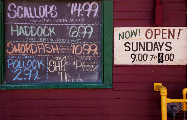 Chalkboard with fish prices and market work hours e at the seafood market in Portland, Maine stock photo
