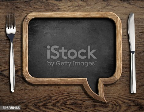 istock chalkboard with fork and knife on wooden dinning table 516289466