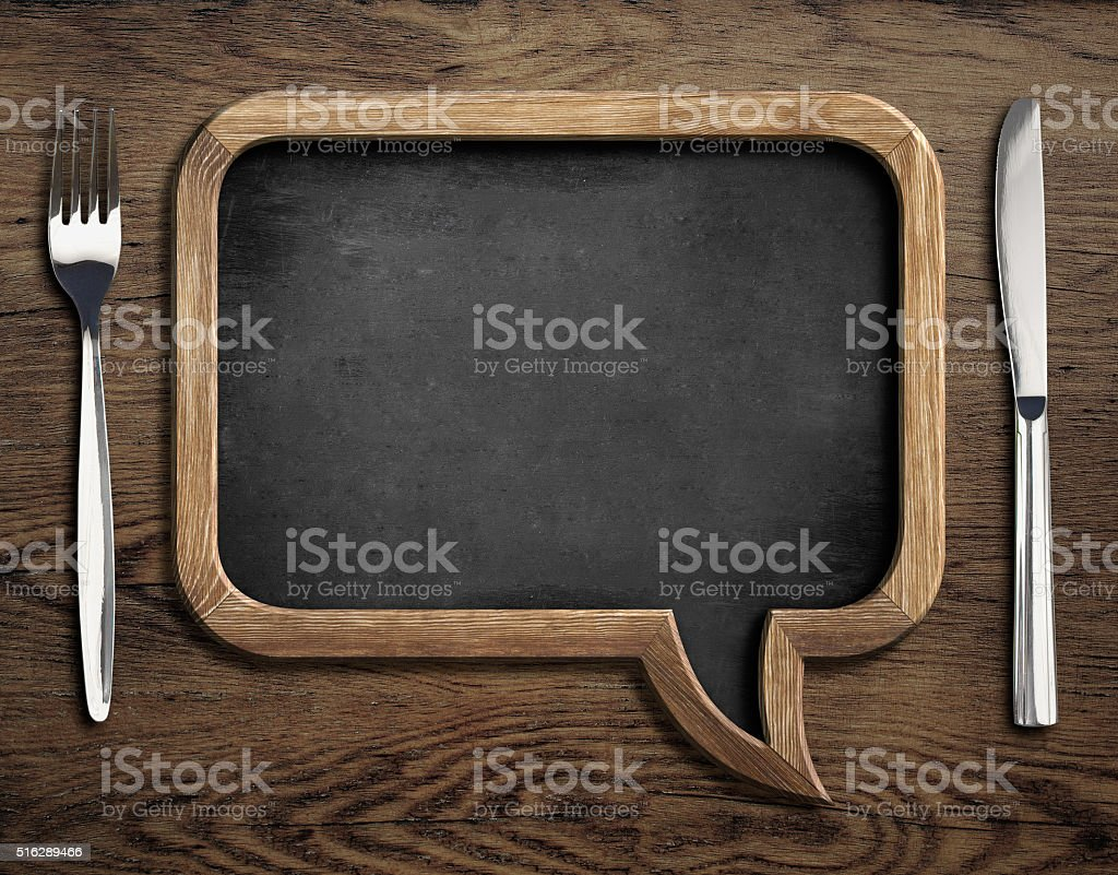 chalkboard with fork and knife on wooden dinning table stock photo