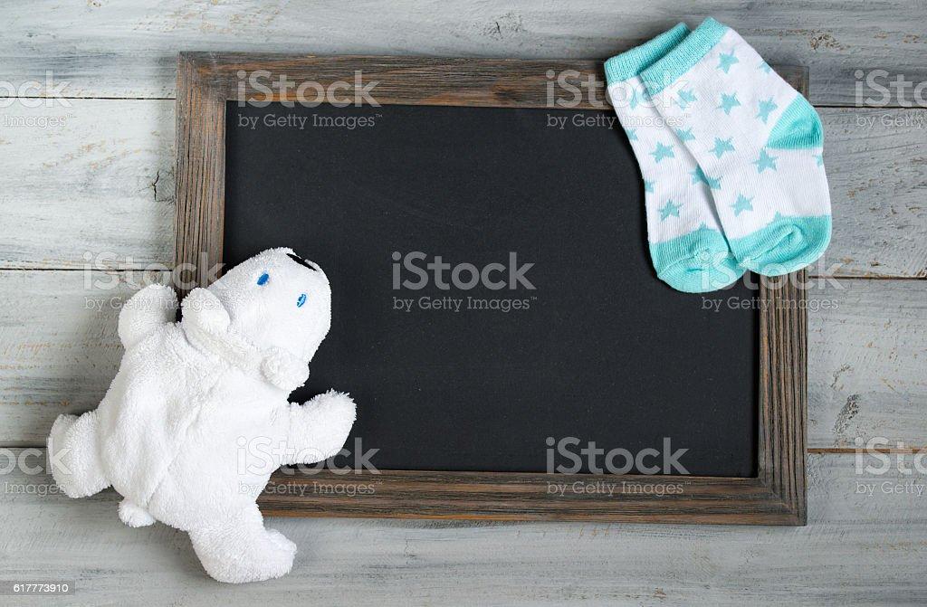 Chalkboard with frame, white toy bear, baby socks stock photo