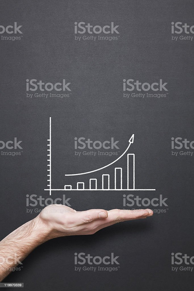 chalkboard with hand and trend chart chalkboard with hand and trend chart Aspirations Stock Photo