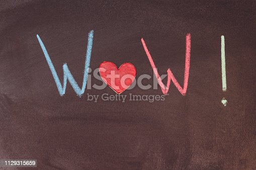 istock Chalkboard with handwriting text WOW. colorful chalk and red wooden heart 1129315659