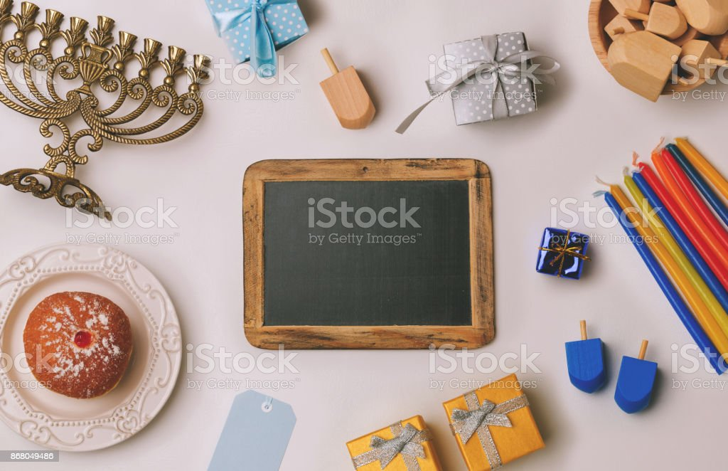 Chalkboard with menorah and sufganiyot over white background. Retro filter effect. View from above stock photo