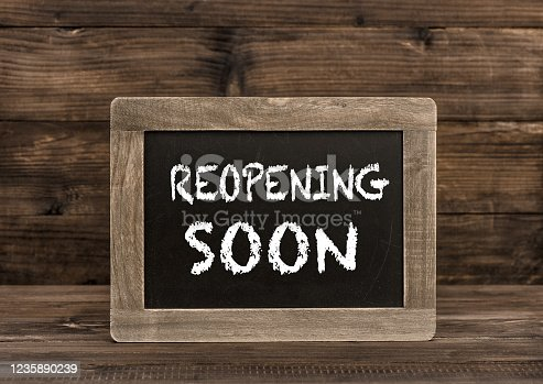 istock Chalkboard wooden background Reopening soon 1235890239