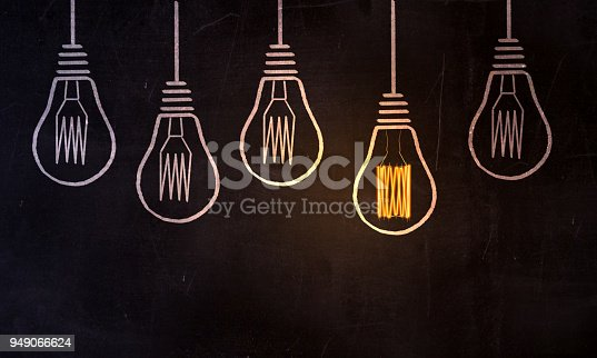 A glowing light bulb between the chalky light bulbs on blackboard, can be used in education, science, business strategies and individuality concepts. ( 3d render )