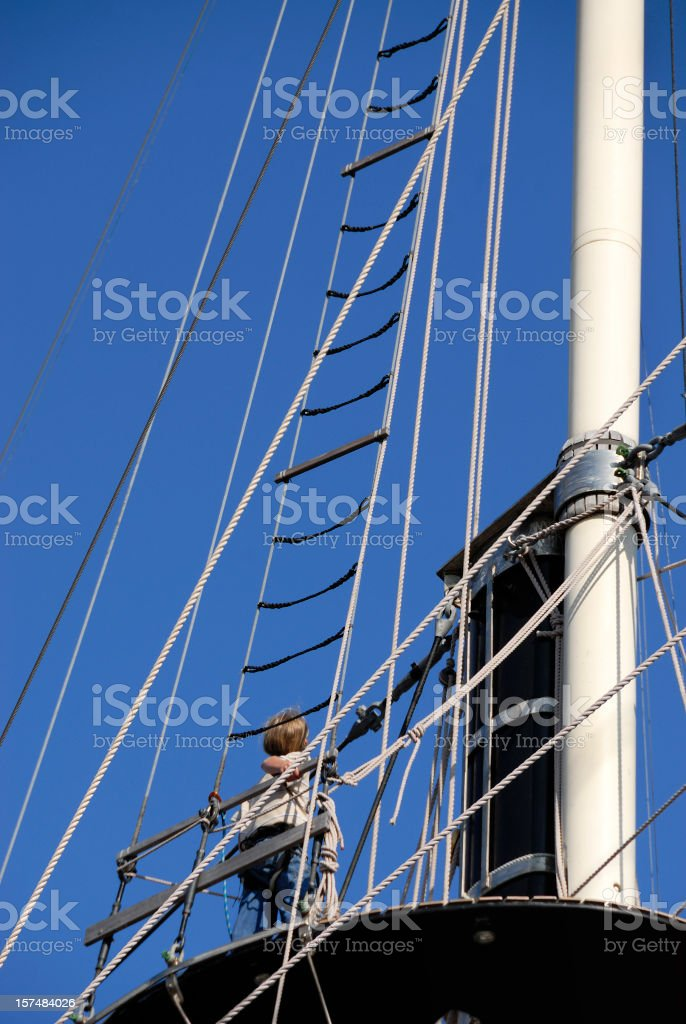 Challenge Contemplation: Youth on Ship Rigging Climbing Higher Decision Point stock photo