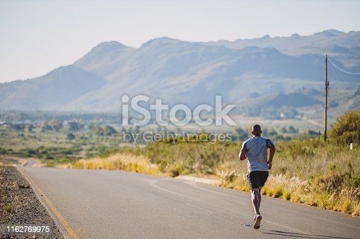 Shot of a sporty young man out running on a country road