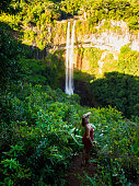 Chamarel Waterfall and happy woman in the tropical jungle of Mauritius