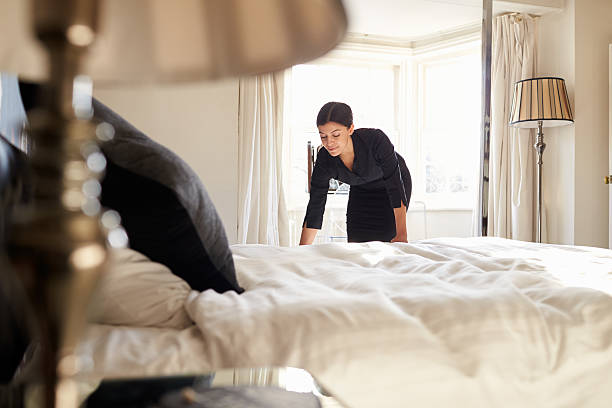 chambermaid changing bed linen on the bed in a hotel room - maid stock pictures, royalty-free photos & images