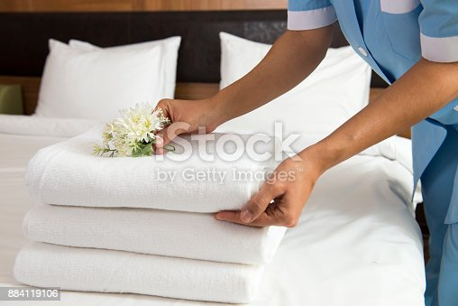 Maid making bed in hotel room. She is